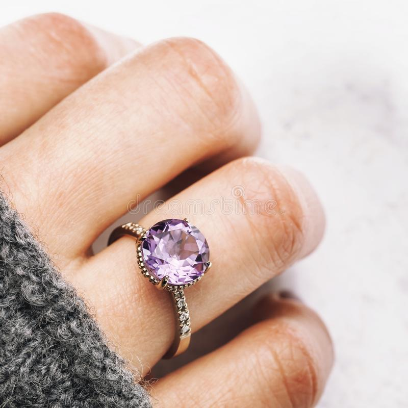 Beautiful white gold hand ring with amethyst and small diamonds. Gemstone close-up stock photography