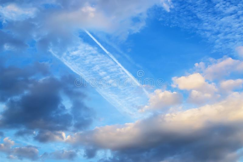 Beautiful white and gray fluffy clouds high in a blue sky. Skyscape with wide airplane trace on a day stock photos