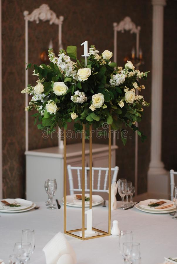 Beautiful White and Green Flower Decoration Arrangement on Wedding Table Golden Support . Wedding Bridal Flower Decoration. stock image