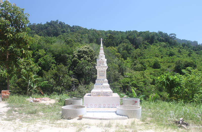 A beautiful white house of spirits in the form of carved tower on the mountain road through the jungle in Koh Samui in Thailand royalty free stock photo