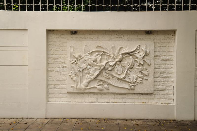 Beautiful white Java stucco patterned on the boundary wall. Vintage white wall bas-relief stucco in plaster, depicts Lotus flower royalty free stock photo