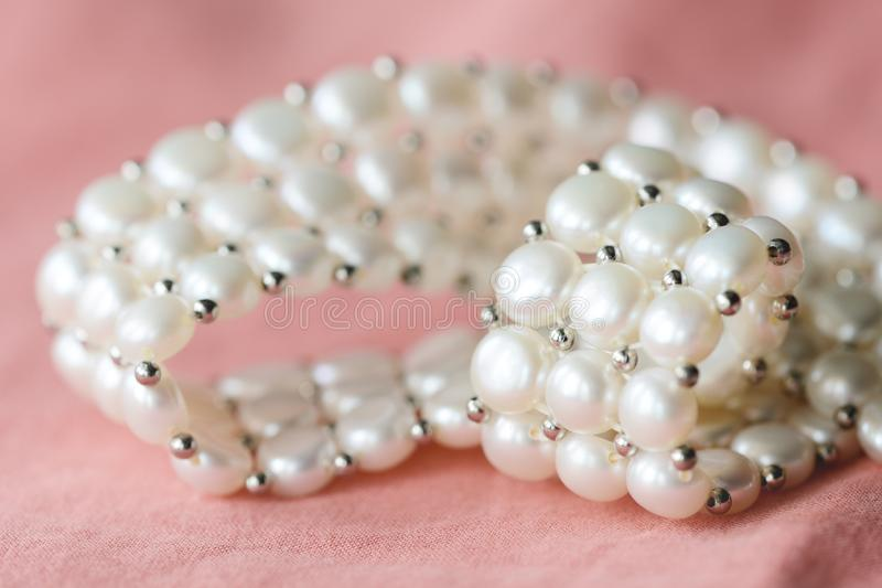 Beautiful white pearl necklace on a coral color textile background. Close up stock photography