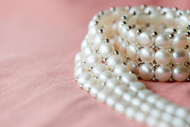 Beautiful white pearl necklace on a coral color textile background. Close up royalty free stock image