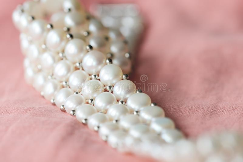 Beautiful white pearl necklace on a coral color textile background. Close up royalty free stock photos