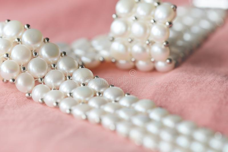 Beautiful white pearl necklace on a coral color textile background. Close up stock photos