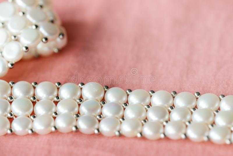 Beautiful white pearl necklace on a coral color textile background. Close up stock images
