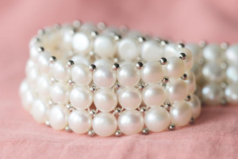 Beautiful white pearl necklace on a coral color textile background. Close up royalty free stock photography