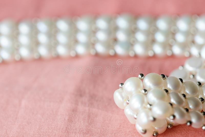 Beautiful white pearl necklace on a coral color textile background. Close up royalty free stock photo