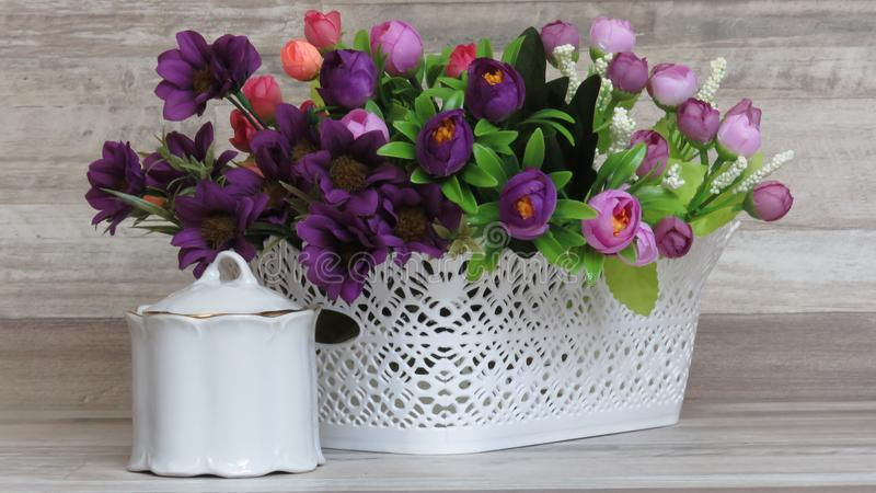 Home decoration. Beautiful White Plastic basket and Artificial Flowers.. A Beautiful Purple Bunch of Artificial Flowers in a White Plastic Busket and a Small royalty free stock photos