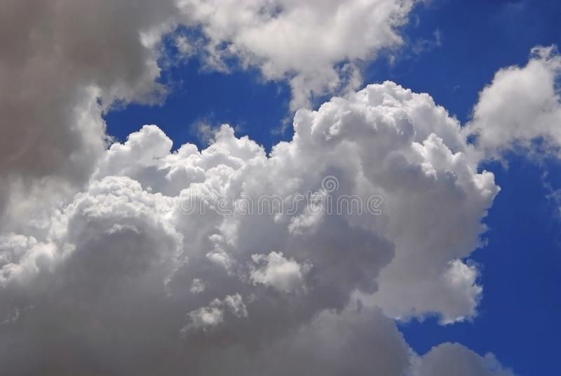 White puffy clouds in blue sky royalty free stock images