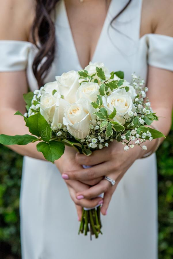Beautiful white rose bouquet with baby`s breath held by a bride with dark hair wearing a white wedding dress and an engagement rin stock photos