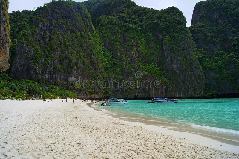 Beautiful white sandy beach beside the blue ocean surrounded by the treed rocks. Thailand. Beautiful white sandy beach beside the blue ocean surrounded by the royalty free stock photography