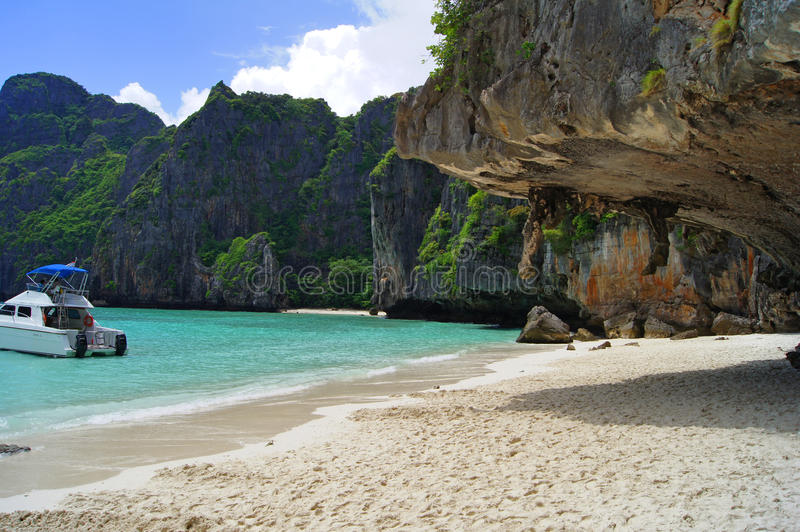Beautiful white sandy beach beside the blue ocean surrounded by the treed rocks. Thailand. Beautiful panoramic view of the white sandy beach beside the blue stock photography
