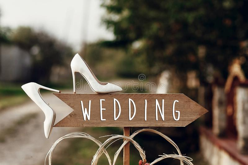 Beautiful white shoes on wooden arrow with wedding text sign. ru royalty free stock image