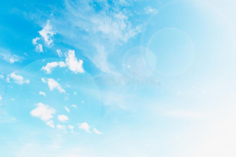 Beautiful white small soft fluffy clouds on a blue sky background, sky with sun glare. Copy space stock photography
