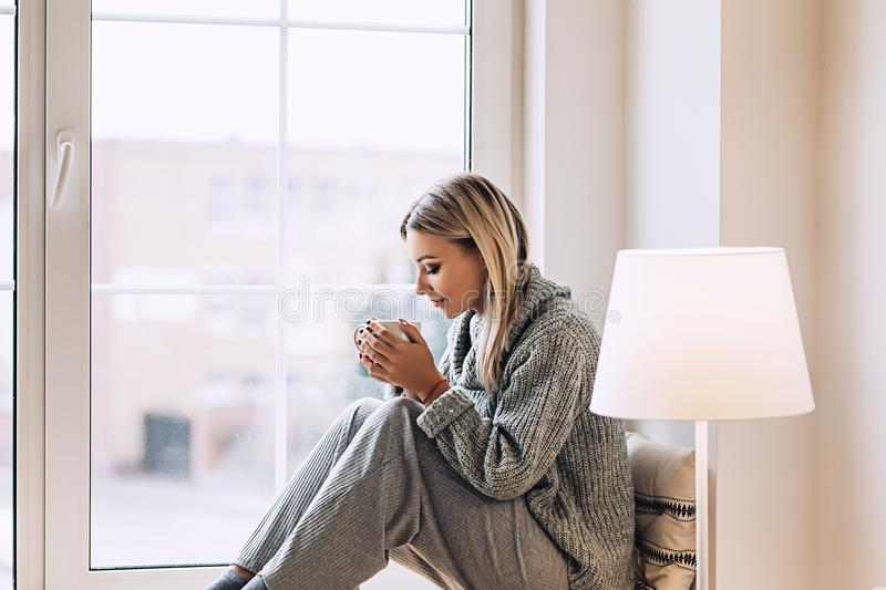 Beautiful white stylish woman in cozy scandinavian interrior sits at home near the big window, portrait of the beautiful royalty free stock images