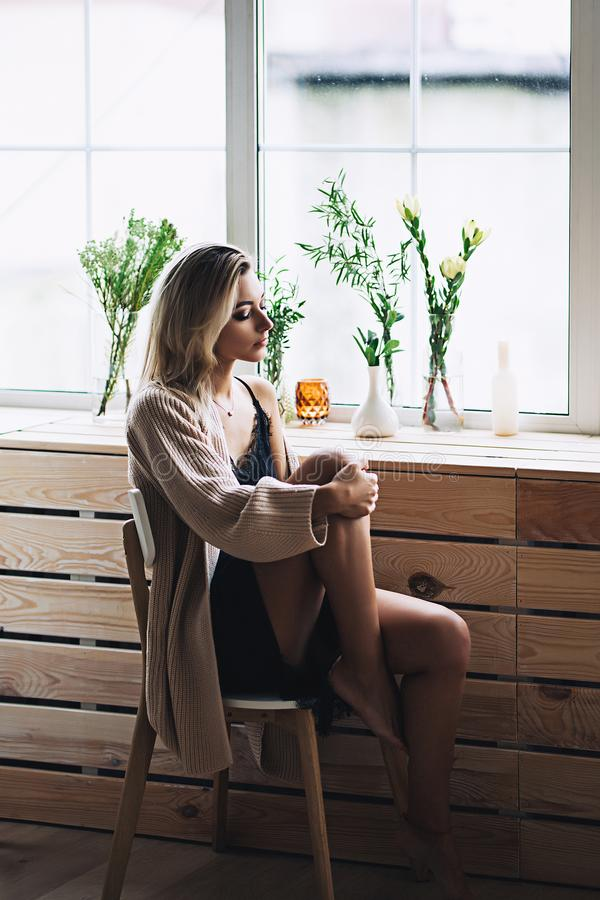 Beautiful white stylish woman with long nacked legs in cozy scandinavian interrior sits at home, portrait of the stock photos