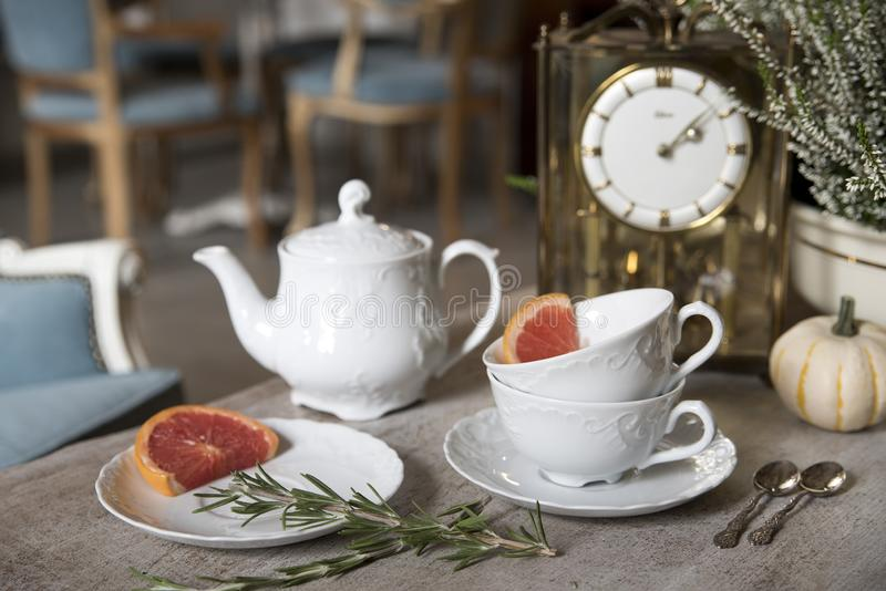 Beautiful white teapot, cups and saucer, antique clock, pumpkin, heather, rosemary and grapefruit. Still life. royalty free stock images