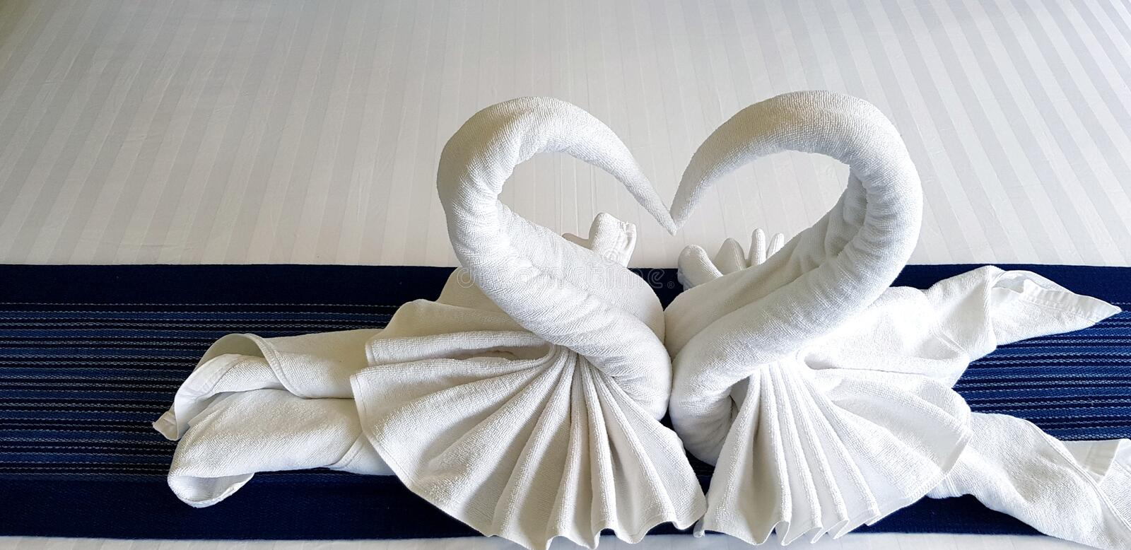 Beautiful White towel folded in heart or two swan shape on bed in bedroom of hotel stock photos