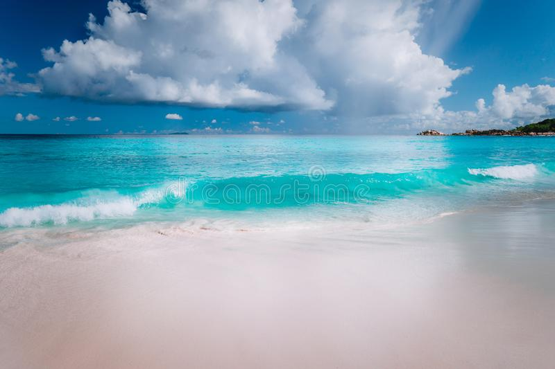Beautiful white wave rolling towards tropical sandy beach. Gorgeous fluffy clouds above blue sea. Seychelles Grand Anse stock photo