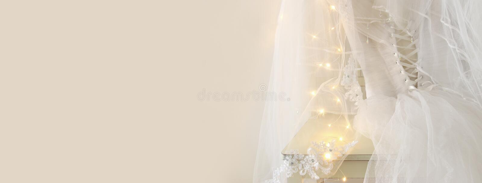 Beautiful white wedding dress and veil on chair with gold garland lights royalty free stock photo