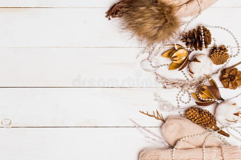 Beautiful white wooden Christmas background for copy space. Winter cones, branches, beads, cotton and women`s mittens on the tabl royalty free stock photography