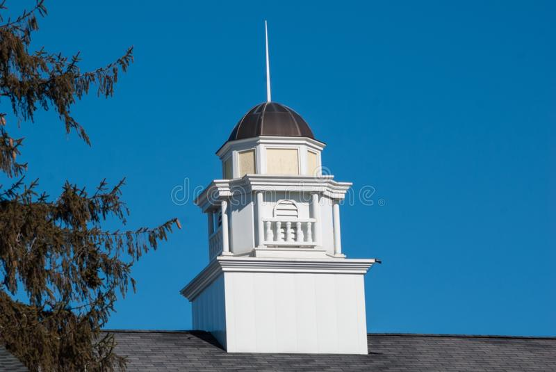 Beautiful white and yellow cupola with brown tin roof against a deep blue sky stock image