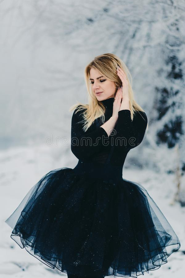 A beautiful young woman in a black dress in winter forest royalty free stock images