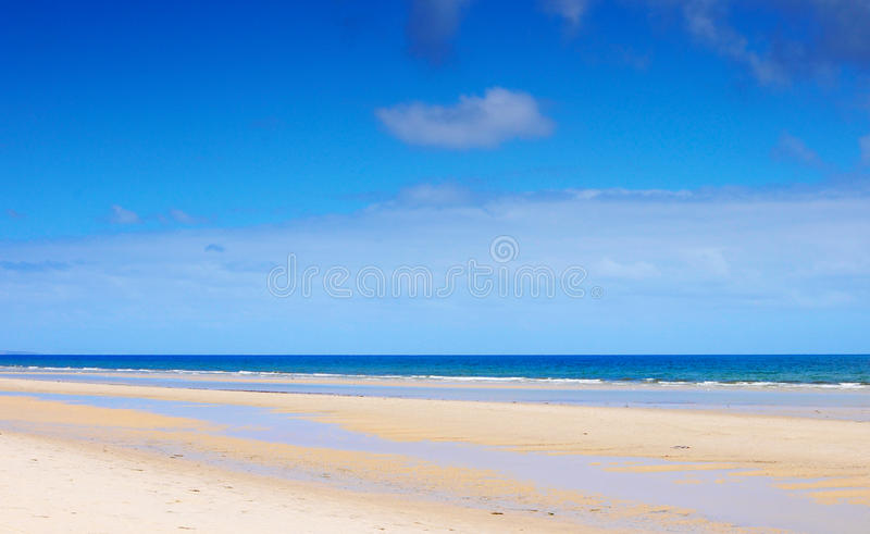 Beautiful wide open beach with blue skies in Summer stock image