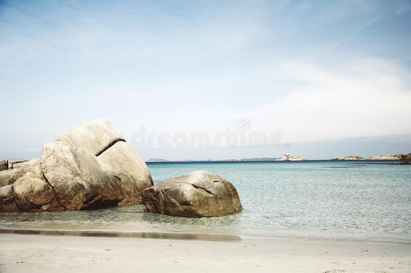 Beautiful wide shot of brown rocks on the body of water under a clear blue sky. A beautiful wide shot of brown rocks on the body of water under a clear blue sky royalty free stock image