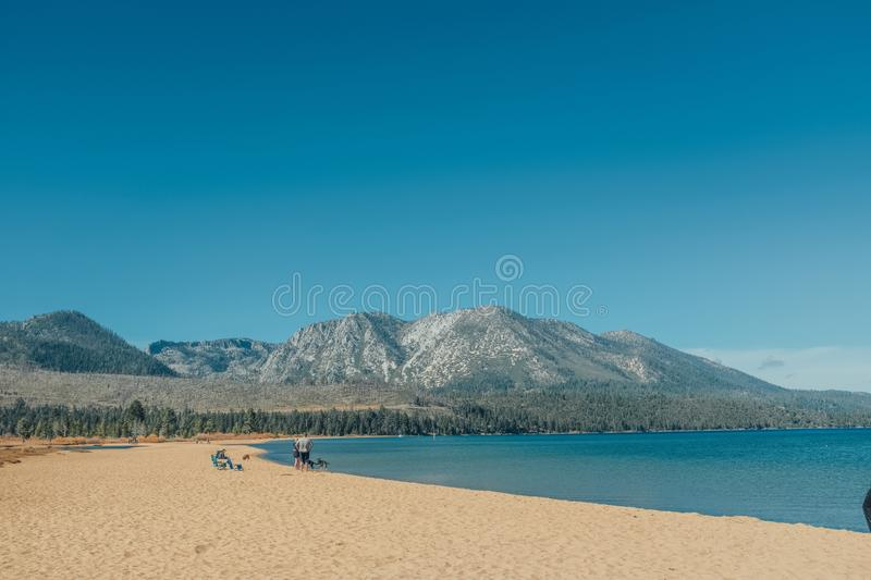 Beautiful wide shot of the Lake Tahoe and mountains in the background with blue sky. A beautiful wide shot of the Lake Tahoe and mountains in the background with stock photos