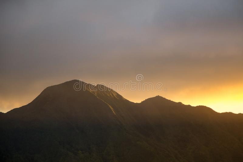 Beautiful wide shot of rocky mountains and hills at sunset with grey clouds and sunlight on the side stock photos