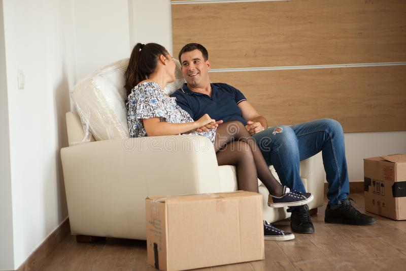 Beautiful wife and husband resting on their sofa in the new flat royalty free stock photos