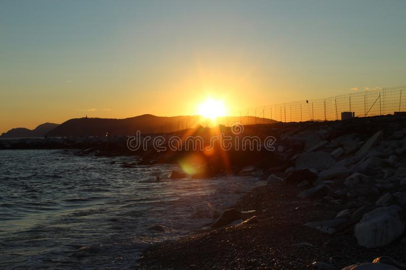 Beautiful wild beach with azure sea, waves on the shore in Tuscany, Italy. Sunny day at the beach. The sunset with the beautiful colours royalty free stock images