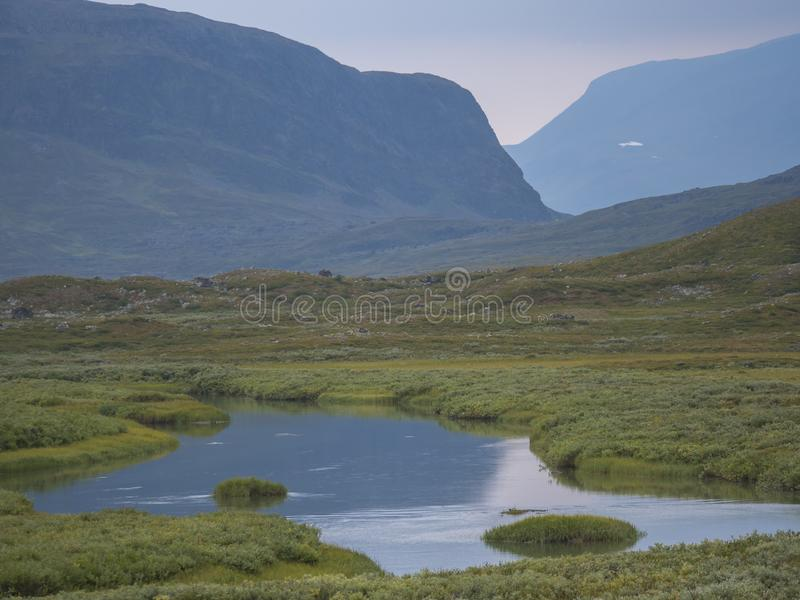 Beautiful wild Lapland nature landscape with blue glacial river, birch tree bushes, snow capped mountains and dramatic clouds. stock images