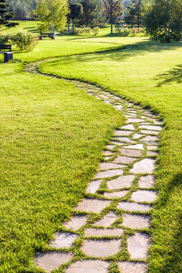 Beautiful winding pathway in a natural park in summer. Beautiful pathway in a natural park in summer. Landscape with scenic winding footpath in sunlight. Stone stock photography