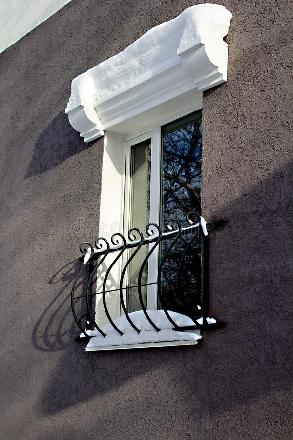 Beautiful Window with black decorative bars and white stucco. In winter stock photography