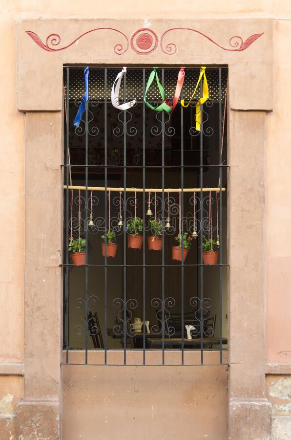 Nice window with colored ribbons, bells and small plants in a street in downtown Queretaro, Mexico. Beautiful window with colored ribbons, bells and small plants royalty free stock images