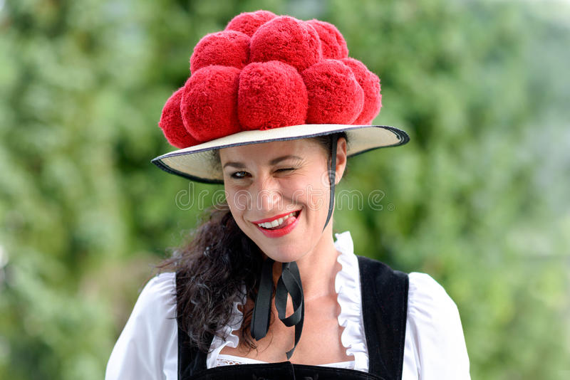 Beautiful winking german woman wearing bollenhut. A portrait of a beautiful german woman wearing traditional clothing and a bollenhut licking her teeth stock images