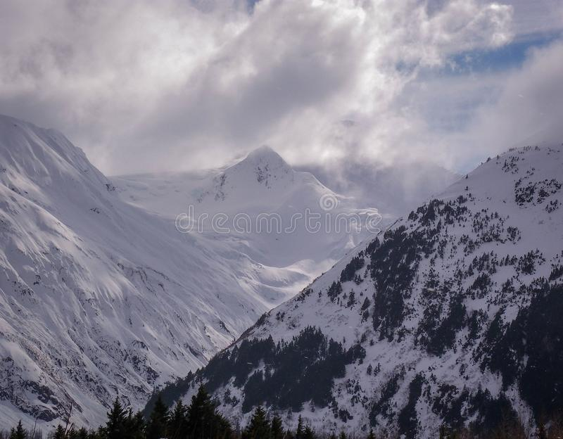 Beautiful winter day with frozen lake, glacier and snowy mountains royalty free stock photography