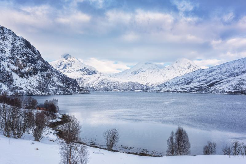 Beautiful winter daytime landscape with lake, snowy mountains and blue cloudy sky stock image