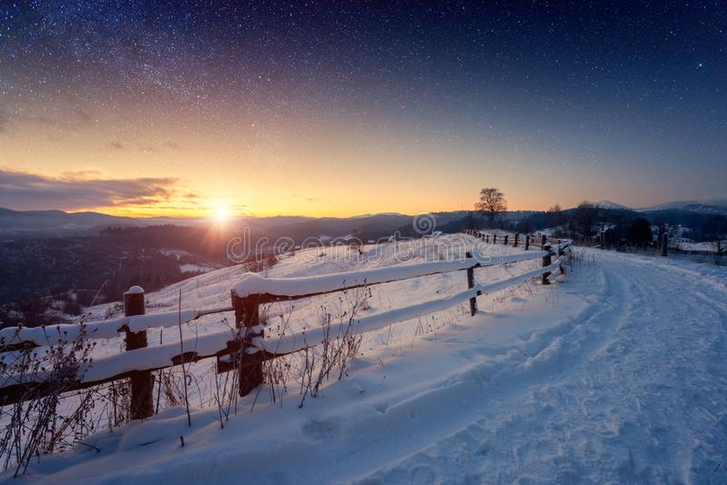Beautiful winter fairytale landscape, stars and rising sun over the snowy mountain road. Fairytale alpine countryside royalty free stock photo