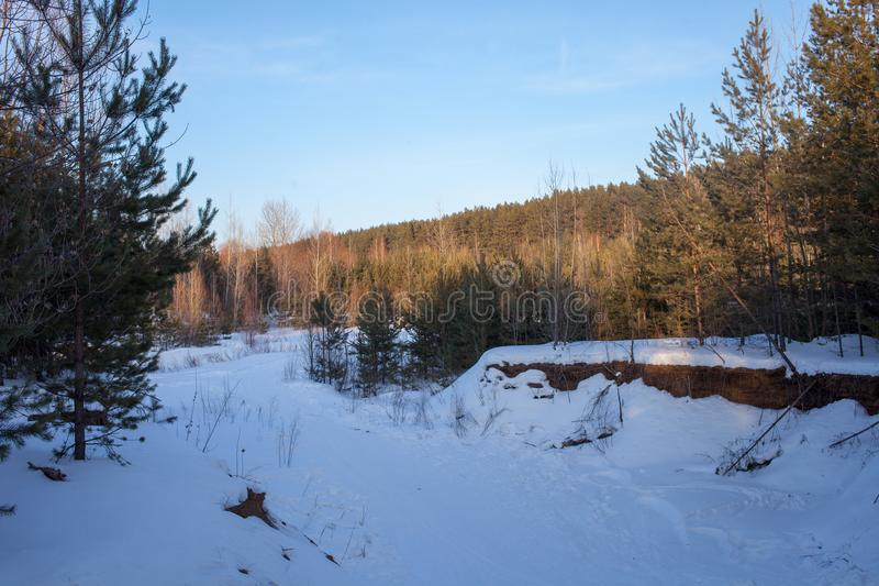 Beautiful winter landscape with forest, river and blue sky. A cold winter day. stock images