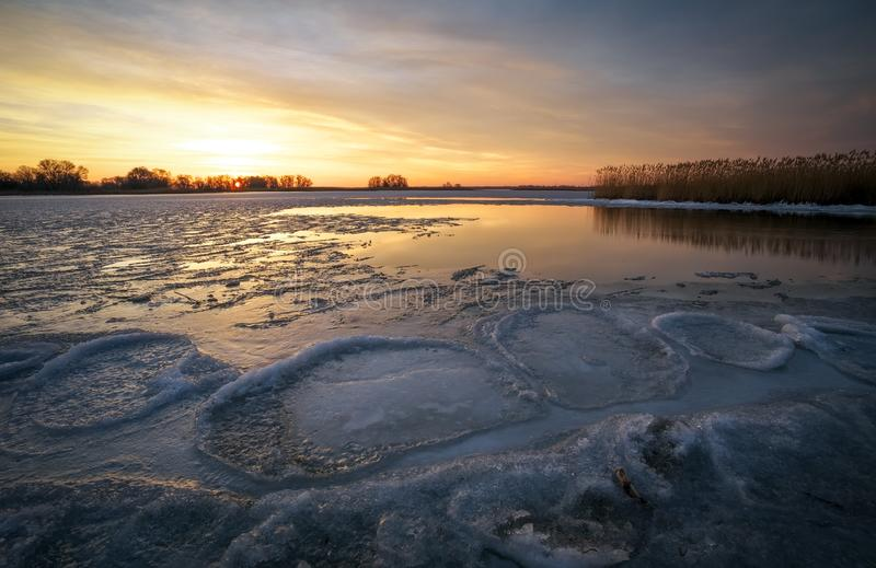 Beautiful Winter landscape with frozen river, reeds and sunset sky. Composition of nature royalty free stock image