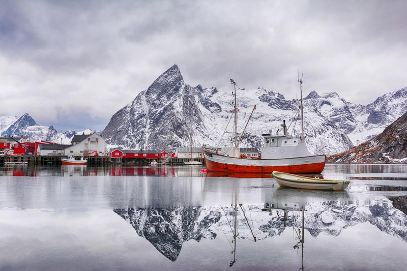 Beautiful winter landscape of harbor with fishing boat and traditional Norwegian rorbus royalty free stock image