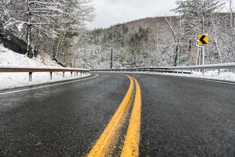 Beautiful winter landscape with highway road with turn and snow-covered trees. Clean mountain asphalt winter road with yellow marking double lines and sign stock images