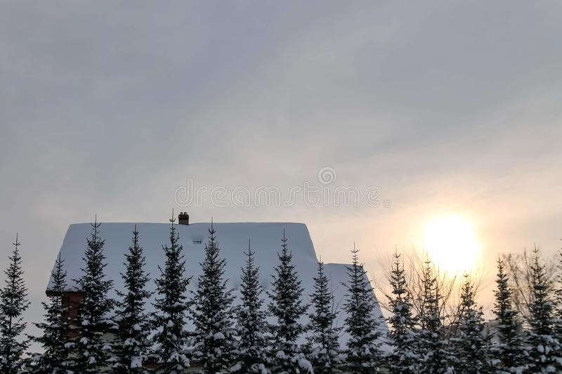 Beautiful winter landscape with a house and fir trees. Snow covered house roof stock image