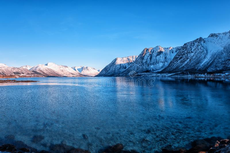 Beautiful winter landscape, lake with snowy mountains with serene blue sky, natural travel outdoor background, Lofoten Islands royalty free stock photos