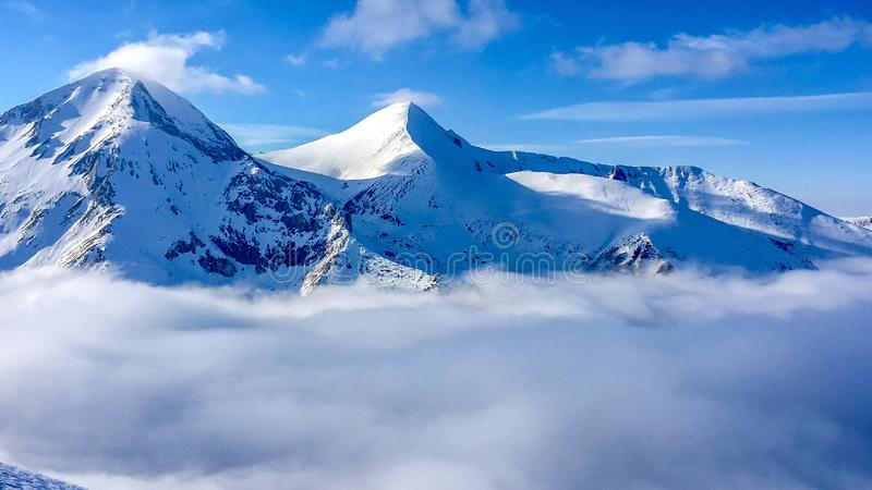 Beautiful winter landscape with snowy mountain peaks, foggy clouds under it and bright blue sky above. stock photography