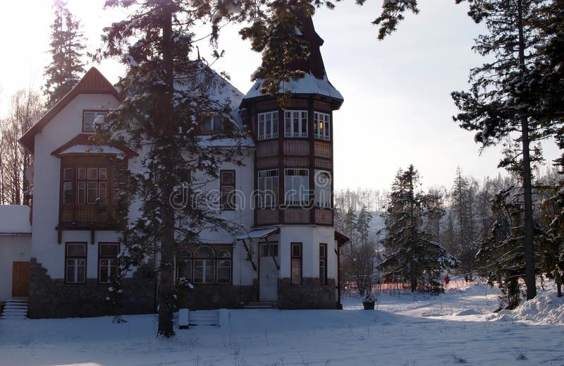 Beautiful winter landscape: a snowy road, trees in the snow, a hotel in the ski resort Tatranská Lomnica stock images